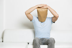 Nędzny anonimowy mężczyzna z głową zakrywał obsiadanie na kanapie. zdjęcia royalty free