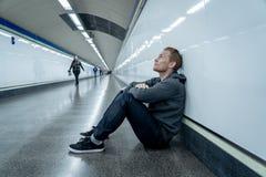 Nędzny bezrobotny młodego człowieka płaczu narkomanu bezdomny w depresji stresuje się obsiadanie na zmielony uliczny metro tunelu fotografia stock