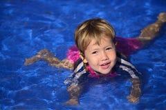 游泳教训:逗人喜爱的女婴n水池 免版税库存照片