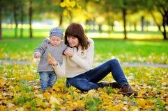 有她的小男婴的n年轻母亲在秋天 图库摄影