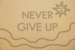N'abandonnez jamais le mot avec le soleil de sourire et ondulez sur le sable Images stock