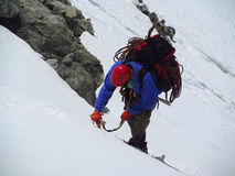 Alpinist climber walking on the top of the mountain through the snow Stock Photos