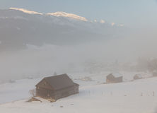N cabins in fog with mountain tops  sticking out Stock Photography