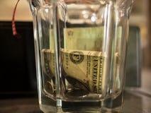 ??n dollar en muntstukken in een glas gefacetteerd glas royalty-vrije stock afbeelding