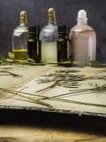 N?dv?ndig olja f?r arom och kosmetisk flaska bland torkade blommor, medicinsk ?rtvariation Naturlig sk?nhetsmedel och skincare so arkivfoto