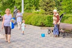 N?dzarska starsza kobieta pyta dla datk?w na bulwarze blisko rze?by Czerwonego wojska ?o?nierz Sukhov fotografia royalty free