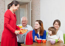 N family communicate over tea with cakes at home Stock Photo