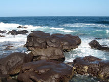 N'gor island coast. N'got island dark rock coast near Dakar in Senegal in Africa Royalty Free Stock Photo