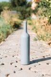 ??n grijze fles op de weg van de tegels, het dorp, landelijk alcoholisme, dronkenschap alcoholische ziekte wijn natuurlijke drank stock foto