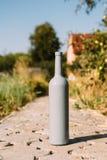 ??n grijze fles op de weg van de tegels, het dorp, landelijk alcoholisme, dronkenschap alcoholische ziekte wijn natuurlijke drank stock fotografie