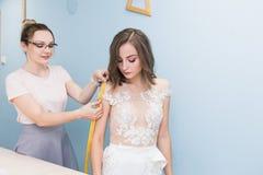 N?hende Werkstatt N?herin bei der Arbeit N?herin nimmt Ma?e eines Heiratskleides lizenzfreie stockfotos