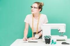 N?hende Werkstatt N?herin bei der Arbeit Portr?t einer jungen Damenschneiderin mit Notizbuch auf einem farbigen Hintergrund lizenzfreie stockbilder