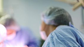 N the hospital operating room. A diverse team of professional surgeons and nurses, a suture wound after a successful