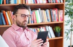 ??n mens die een boek in een zitting van de ebooklezer op een laag thuis lezen royalty-vrije stock foto