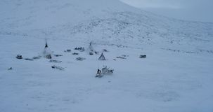 N the middle of tundra in Siberia a big camp of yurts in the evening making fire inside sleigh and reindeers outside stock video footage