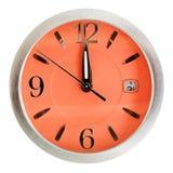 Één minuut aan twaalf uur op oranje wijzerplaat Stock Foto