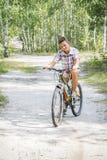 N o verão, na floresta, um menino monta uma bicicleta na estrada fotografia de stock