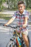N o verão, na floresta, um menino monta uma bicicleta na estrada imagens de stock