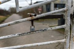 N old iron gate is secured with a padlock. An old iron gate is secured with a padlock - concept: security and protection stock photos