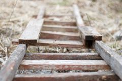 Аn old wooden ladder lying on the ground.  Royalty Free Stock Images