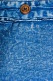 n?r du bekl?r objektbl?tt stonewashed f?r bomullstyg f?r urblekt jeans textur med s?mmar, omfamningar, knappar och nitar, makroen arkivbild