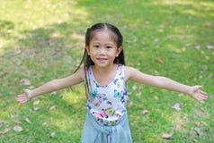 N?r du ler den lilla asiatiska barnflickan ?ppnade hennes h?nder i sommartr?dg?rden arkivfoton