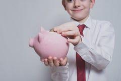N?r du ler pojken s?tter ett mynt i en rosa spargris ?gander?tt f?r home tangent f?r aff?rsid? som guld- ner skyen till Svart bak arkivfoto
