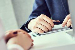 N?ra ?vre fokus p? den manliga handinnehavkulspetspennan och lyssna till kollegan eller anst?lld F?retags lagutbildning arkivbild