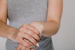 N?ra ?vre foto av sm?rtsamma handleder f?r kvinnligt innehav fotografering för bildbyråer