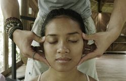N?ra ?vre framsidast?ende av den unga ursnygga och avkopplade asiatiska indonesiska kvinnan som mottar traditionell ansikts- thai arkivfoton