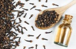 N?ra ?vre glasflaska av kryddnejlikaolja och kryddnejlikor i tr?sked p? den vita lantliga tabellen arkivfoton