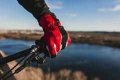 N?ra ?vre sikt av en cyklistutrustninghandske och styre Man som rider cykeln ner Rocky Hill p? solnedg?ngen Extremt sportbegrepp royaltyfri fotografi
