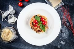 N?ra ?vre sikt p? traditionell italiensk pasta med basilika och den k?rsb?rsr?da tomaten i den vita plattan Plan lekmanna- italie royaltyfria bilder