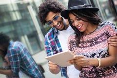 N?ra ?vre st?ende av lyckliga unga svarta par genom att anv?nda en digital minnestavla tillsammans arkivfoto