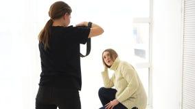 N?rbild av den kvinnliga fotografen som tar bilden av att le modellen i det vita f?rkl?det och m?rk jeans i yrkesm?ssigt foto lager videofilmer