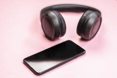 N?rbild av den smarta telefonen med h?rlurar p? en rosa bakgrund royaltyfri bild