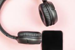 N?rbild av den smarta telefonen med h?rlurar p? en rosa bakgrund royaltyfri foto