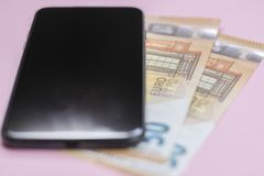 N?rbild av den smarta telefonen med pengar p? en rosa bakgrund royaltyfri foto