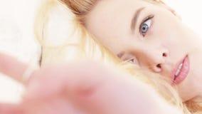 N?rbild av h?rliga ung kvinnas framsida med ?gon f?r perfekt makeup som, f?r blont h?r och bl?tt-och-gr? f?rger ligger p? mjukt o arkivfilmer