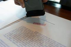 N?rbildbilder av h?nderna av aff?rsm?n som undertecknar och st?mplar i godk?nda avtalsformer royaltyfri foto