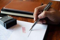 N?rbildbilder av h?nderna av aff?rsm?n som undertecknar och st?mplar i godk?nda avtalsformer royaltyfri fotografi