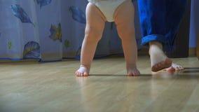 N?rbilden av barn` s l?gger benen p? ryggen ta deras f?rsta steg lager videofilmer