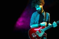 N?rbildfoto av hipstermannen med den r?da gitarren i neonljus leka rock skjuten studio f?r elektrisk gitarrmusiker arkivfoton