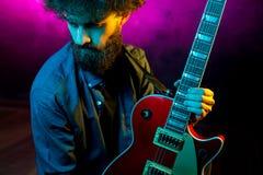 N?rbildfoto av hipstermannen med den r?da gitarren i neonljus leka rock skjuten studio f?r elektrisk gitarrmusiker fotografering för bildbyråer