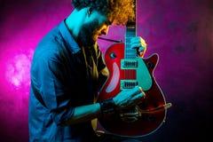 N?rbildfoto av hipstermannen med den r?da gitarren i neonljus leka rock skjuten studio f?r elektrisk gitarrmusiker royaltyfri bild
