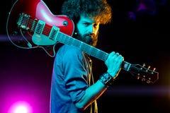 N?rbildfoto av hipstermannen med den r?da gitarren i neonljus leka rock skjuten studio f?r elektrisk gitarrmusiker arkivfoto