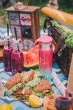 N?rbildpicknick i natur Sm?rg?sar, kaka, termos, drinkar och druvor arkivfoton