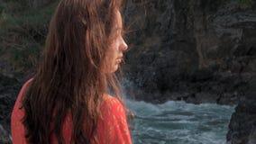 N?rbildsikten av unga flickan i r?tt kl?nninganseende n?ra att sl? f?r stormv?gor vaggar unga flickan som ut ser till havet arkivfilmer