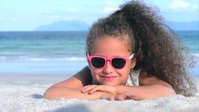 N?rbildst?ende av en h?rlig liten flicka i rosa exponeringsglas, gulligt le se kameran som f?rbi ligger p? sanden arkivfilmer