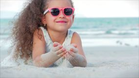 N?rbildst?ende av en h?rlig liten flicka i rosa exponeringsglas, gulligt le se kameran som f?rbi ligger p? sanden lager videofilmer